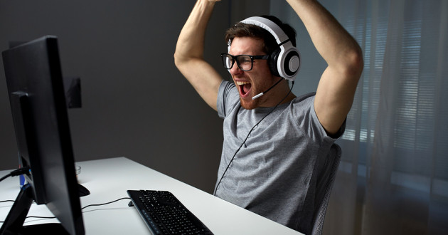 A young man raising his arms in celebration while playing a computer game.