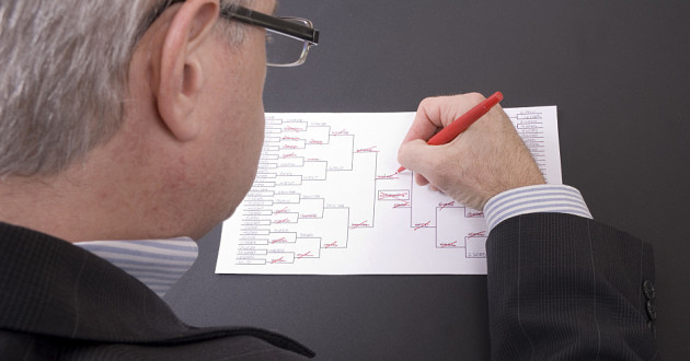 A businessman filling out a bracket for a sports tournament.