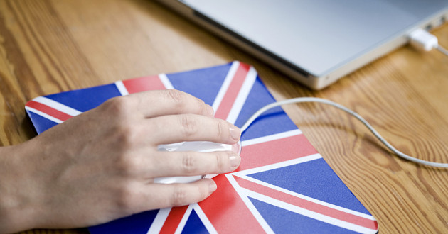 A person using a laptop with a Union Jack mouse pad.