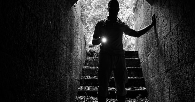 Young man with a flashlight in a stone tunnel