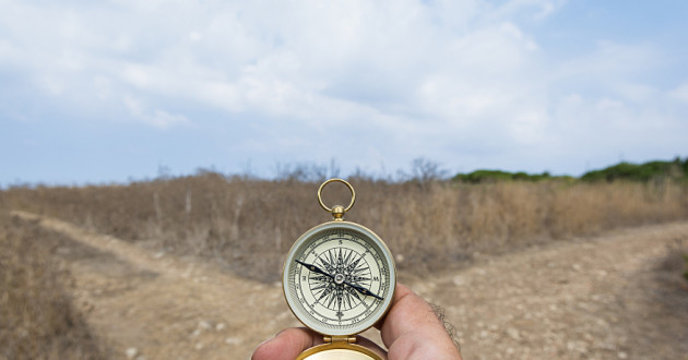 A hand holding a compass before a fork in the road.