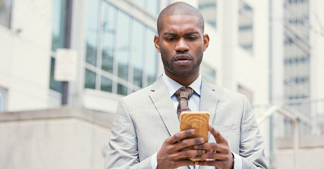 A businessman holding a smartphone with a puzzled expression.