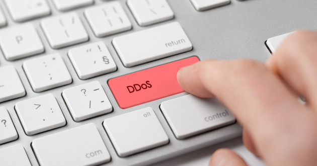 """A finger pressing a computer key labeled """"DDoS."""""""