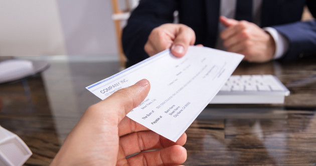 A businessperson handing an employee a paycheck.