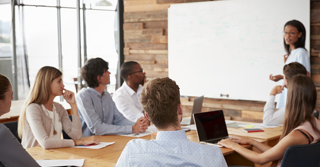 An instructor trains a group of people in a modern meeting room: skills gap