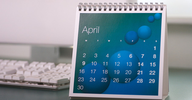 An April calendar in front of a desktop computer.