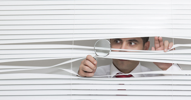 A businessman peeks through blinds with a magnifying glass: insider threats