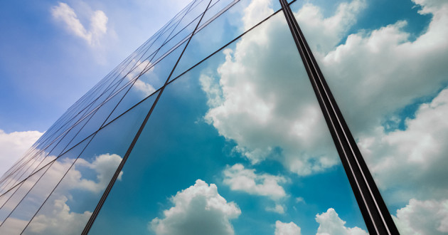 A reflection of clouds in a large, modern office building: cloud security solutions