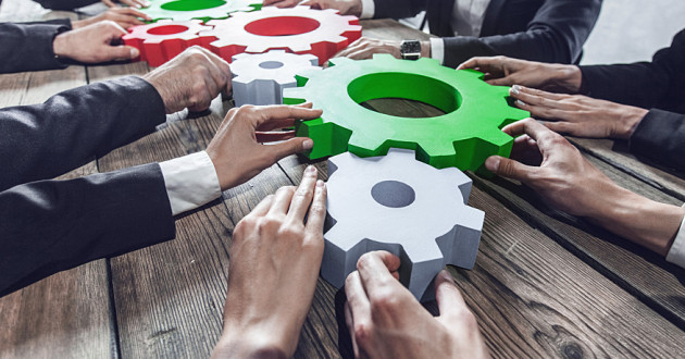 Businesspeople assemble large, colored gears on a wooden table: collaborative defense