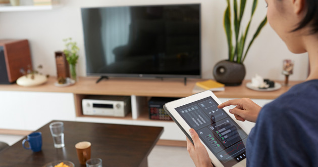 A woman using a digital tablet to control a smart home system: IoT