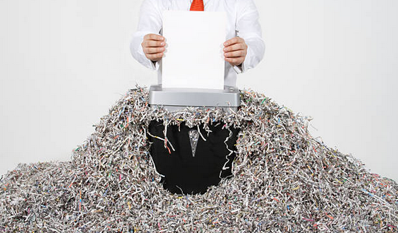Man using paper shredder and surrounded by shredded paper.