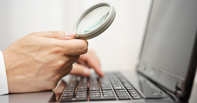 A hand holding a magnifying glass up to a laptop screen.