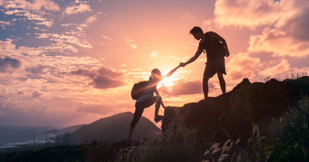 A hiker helps another hiker up a cliff at sunset: secure partnerships