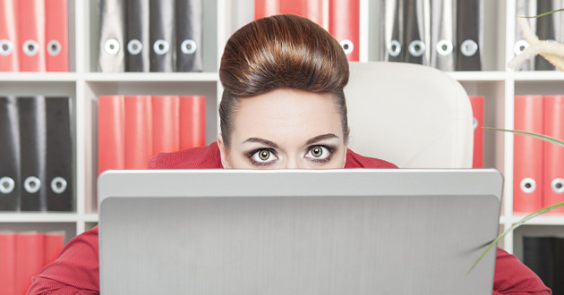 A businesswoman peering over a laptop in an office.