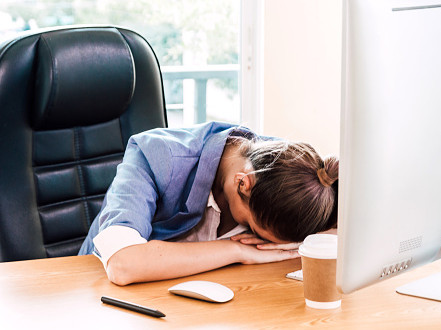An office employee rests her head on her desk at the office: security awareness