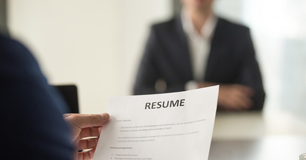 A person reading a resume while interviewing a job candidate.