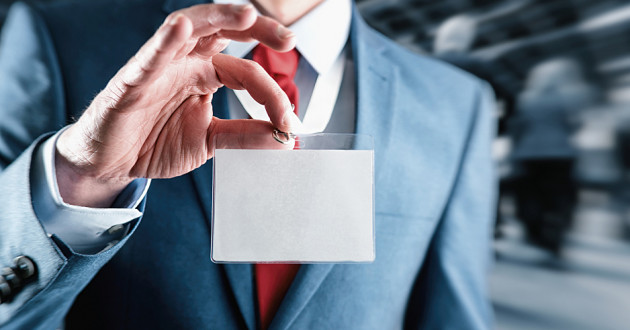 A businessman holds a blank ID card: privileged account management