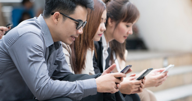 Businessmen and businesswomen using smartphones, oblivious to the mobile threat