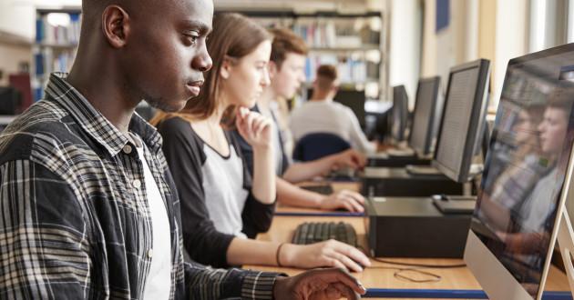 Students using desktop computers in a classroom: hacker highschool