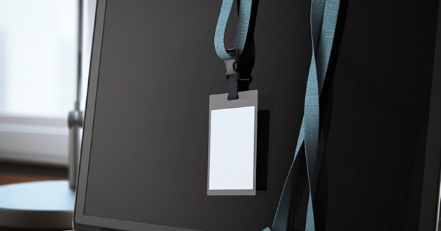 An ID badge hanging from a blue lanyard draped over a laptop monitor: privileged accounts