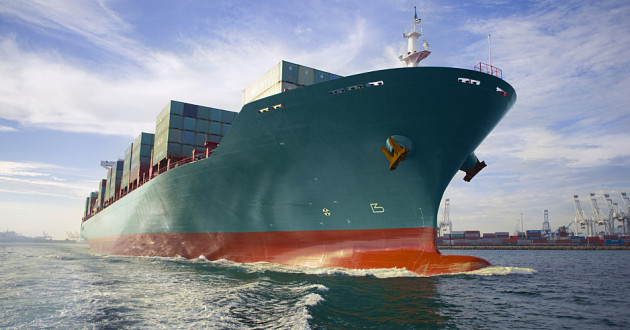 A loaded cargo ship sailing out of port.