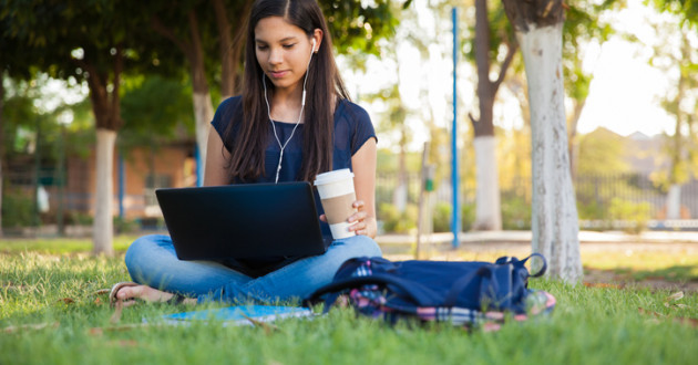 Teen girl using a laptop outside: hacking skills
