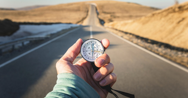 A hand holding a compass before a paved road: GDPR