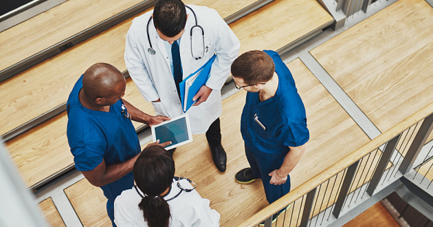 Healthcare professionals stand in a corridor to discuss a patient's condition: healthcare cybersecurity