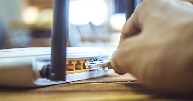 A hand plugging a cable into a Wi-Fi router: Wi-Fi security
