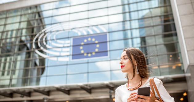 A businesswoman using a smartphone outside a building displaying an EU flag in the window: GDPR