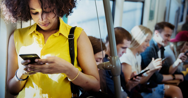 Several passengers using smartphones on a bus: privacy