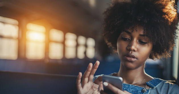 A woman using a smartphone on a train: mobile app security
