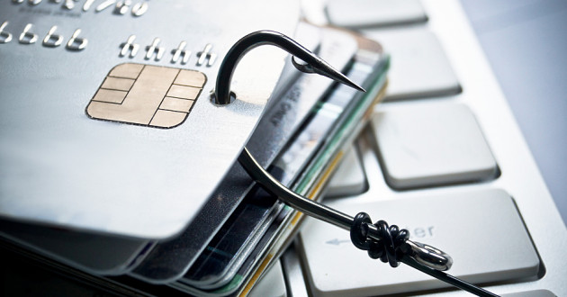 A fish hook and a stack of credit cards on a computer keyboard: phishing campaign