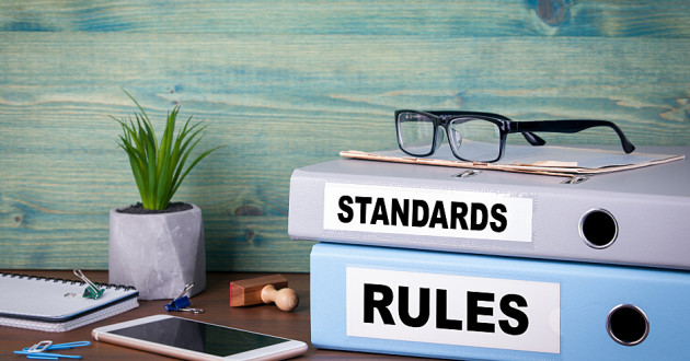 Two large notebooks labelled standards and rules: security risk management