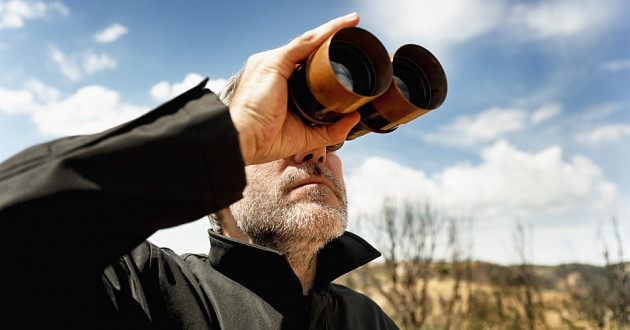 Close-up photo of a person looking through binoculars: threat hunting