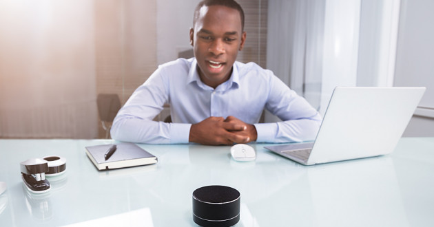 A man speaking into a smart speaker at work: smart office