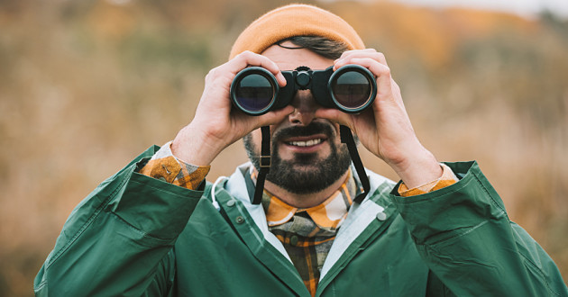 A man using binoculars outdoors: threat hunting
