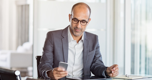 A businessman using a smartphone in a modern office: privileged access management