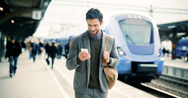 A businessman using a smartphone at a train station: endpoint security