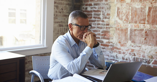 A professional thinking while using a laptop in an office: SIEM