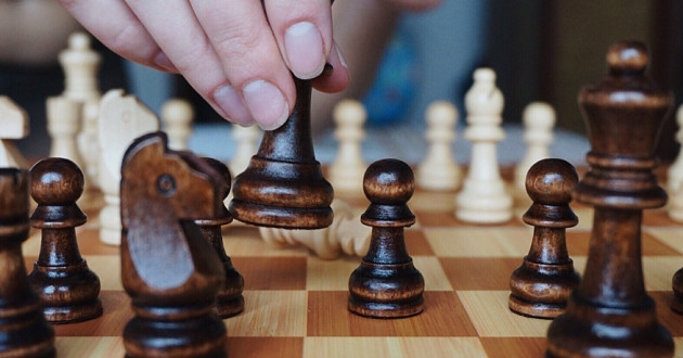 A hand moving a pawn forward on a chess board: cybersecurity game