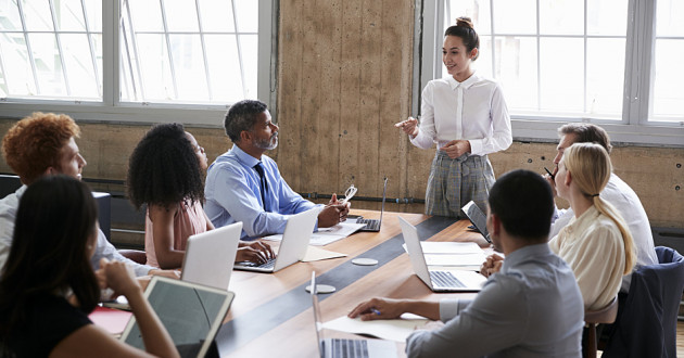 A businesswoman addressing employees in a conference room: security managers