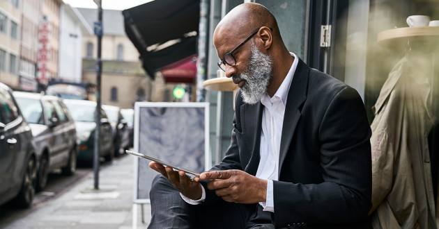 A businessman using a digital tablet outdoors: endpoint management