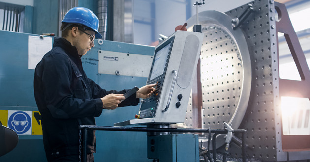 An industrial worker programming a machine with a digital tablet: IoT device management