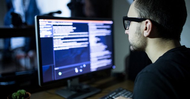 A man typing code on a desktop computer: malware classification