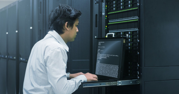 IT engineer working on a laptop in a server room: DNS analytics
