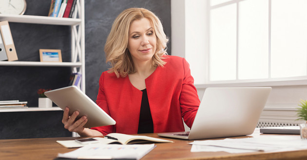 A businesswoman using a digital tablet while typing on a laptop: endpoint management