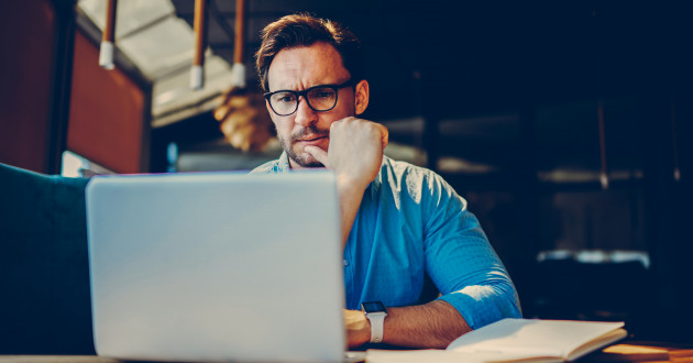 A man frowning while using a laptop: malspam campaign