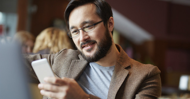 Man using a smartphone in a cafe: digital identity trust.