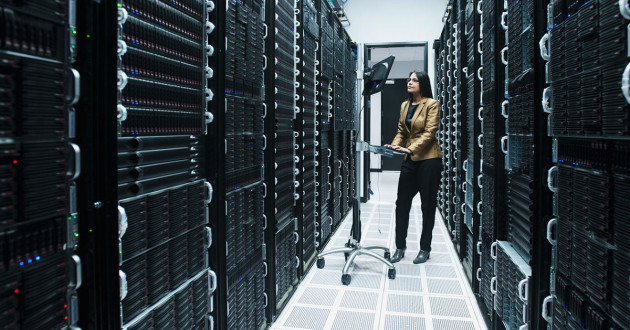Woman working on computer in large server room.